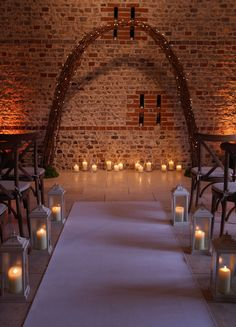 Crossback chairs for a ceremony with an ivory aisle carpet runner, vintage-style lanterns, storm lanterns and twisted willow archway with pealights for a rustic woodland wedding at Upwaltham Barns by www.stressfreehire.com #venuetransformers