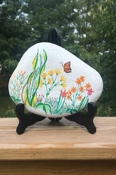 The Flower Garden Hand Painted Rock features a fantasy butterfly along with a multi-color floral display painted on a white background. The back of the rock is left in it's natural state and signed by yours truly. Painted Rocks For Sale, Hand Painted Rocks, Orange Butterfly, River Stones, Stone Painting, Custom Paint, Rock Art, Flowers, Nature