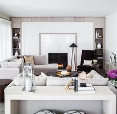 The classic, modern great room features dove-gray velvet and linen-covered Kravet sofas, a custom ivory lacquered sofa table, and custom built-in bookcases. A Powell and Bonnell contemporary wing chair upholstered in a deep mink mohair fabric balances the clean, bright room.