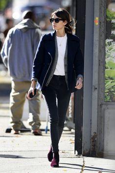 Alexa Chung, en su look tomboy, con pitillos azul marino, Chelsea boots en terciopelo granate, camiseta blanca de algodón, cárdigan gris y pea coat azul.