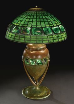 """TIFFANY STUDIOS  """"GEOMETRIC AND TURTLEBACK TILE"""" TABLE LAMP      with an urn-form """"Turtleback Tile"""" base    shade with small early tag impressed TIFFANY STUDIOS/NEW YORK  base impressed TIFFANY STUDIOS/NEW YORK  leaded glass, favrile glass and patinated bronze    23 1/4 in. (59 cm) high   15 7/8 in. (40.3 cm) diameter of shade  circa 1905"""
