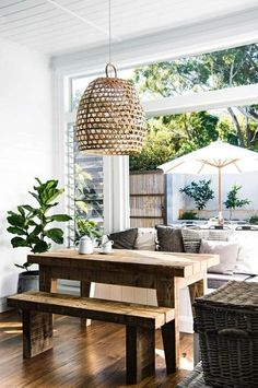 Dining room with wall that opens to backyard - love the rustic wood table with clean lines and the basket hanging lamp.