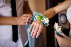 Groom helps wearing flower bracelet