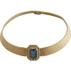 This vintage Grosse Germany necklace features a tight gold tone weave with a rhinestone sapphire at its center.  The rhinestone is in a raised above