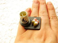 "This is soooo cute ring! It is a cup of ""ocha"" or green tea with ""sansyoku dango"" or 3 colored dumpling. It is just like the green tea you get at sushi restaurants as these restaurants usually use bagged tea. You can see the little bag in the tea!"