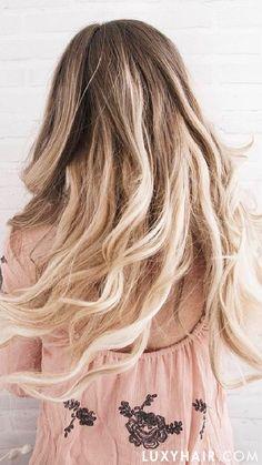Loose flowy mermaid waves, wearing Luxy Hair Blonde Balayage Extensions.