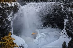 Helmcken - Helmcken Falls in Well Grey Park, BC, Canada.  During the winter an enormous cone of ice and snow forms around the base of the falls, with ice also covering the sides of the canyon and producing an extremely challenging environment for ice climbers. On this occasion climber Will Gadd was being filmed from the helicopter, his line of ascent can be seen as a dark line to the left of the waterfall.