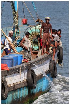 Fishermen Returning - Goa India. I look at the discharge of water and I can't help but wonder if it is a wash down hose, or if they are pumping the bilge to make it to Port? McC