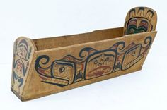 Lot 196- Henry Hunt (1923-1985 Kwakiutl) Attributed Bentwood Cradle Box 13.5''x29''x10''. Finely carved cedar polychrome painted box with sinew binding. Human, Eagle, and Sisiutl motifs on exterior with interior relief carved mask. Slight edge wear, overall excellent condition. Father of Kwakwaka'wakw artists Tony and Richard Hunt. Northwest coast native.