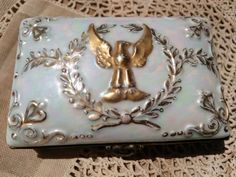 """Gold Eagle Porcelain Box with Laurel Wreath and Bow - Antique Limoges by Montigny & Cie Signed . Rectangle shape . French Empire Napoleon Style.  Early 20th century French porcelain trinket box with hinged lid and ormolu enclosure. The lid is decorated with embossed wreath, bow and Eagle on mother of pearl lusterware with pink and blue shades.  Good vintage condition the mounts was unsealed and glued later, space remains in between.  Size: 2"""" Height by 3 .5"""" Length.5.5 in . = 5.2 x 9 x 14…"""