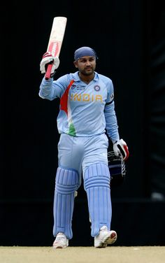 Virender Sehwag raises his bat after scoring a century during a 2007 World Cup match. India Cricket Team, Cricket Sport, 2007 World Cup, Cricket Wallpapers, World Cup Match, Just A Game, Team S, Galaxy Wallpaper, Avengers