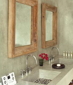 nickel faucet with old-school taps, driftwood mirror frame, polished concrete counter with integral sink, pebble sink (how do you get the toothpaste gunk out of that?)