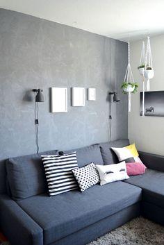 Edler Kontrast im Wohnzimmer: Betonwand trifft moderne Blumenampeln