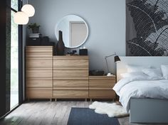 Dormitorio con una cómoda OPPLAND en roble, una cama MALM blanca y una piel de oveja LUDDE blanca.