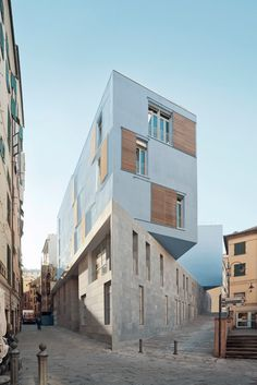 Stone-clad base supports stacked classrooms at PFP Architekten's school in Genoa.