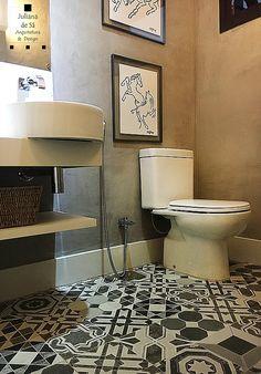 Banheiro com piso geométrico, quadrinhos e o cimento queimado são uma nova tendência.