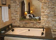 a mirror and rockwork really enhance a corner jacuzzi cabin