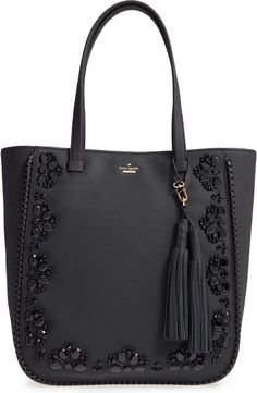 Hand-stitched jet-black beads add just the right amount of glint to this gorgeous pebbled-leather bag by Kate Spade, while laser-cut whipstitched trim beautifully frames the embellished exterior. An optional tassel charm adds a swingy touch to the elegant style.