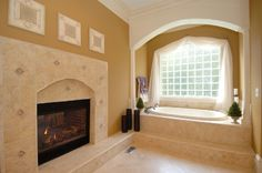 I love the bathtub under the window right next to the fireplace...someday.....