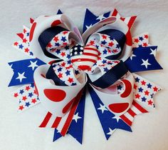 Approximately 6 Inch Loopy Boutique Stacked Hair Bow Spiked Pinwheel Base Patriotic Resin Embellishment. Stars and Stripes, Red, White and Blue Grosgrain Ribbon This Fourth of July, patriotic, stacked