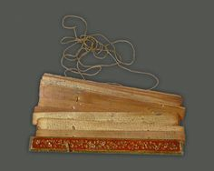 The string passes through holes made in the palm leaf pages of a pothi