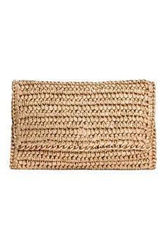Bolsa de palha: Bolsa de palha de papel entrançada com rebordo de metal e aba com fecho magnético e fecho éclair. Forrada. Medidas: 16x24 cm.