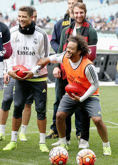 Cristiano Ronaldo and Marcelo of Real Madrid react while holding an AFL football during a Real Madrid training session at Melbourne Cricket Ground on July 17, 2015 in Melbourne, Australia.
