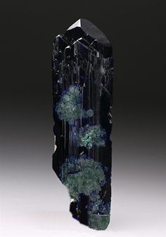 A substantial well formed lustrous bladed crystal of Tsumeb Mine Azurite measuring 8cm tall, displaying a rich dark royal blue colour with parallel growth and some green alteration to Malachite. Some chipping is apparent but this does not detract from a fine Tsumeb Azurite.