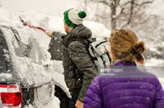 Stock Photo : Couple cleaning snow covered on car