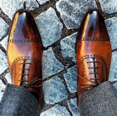 Brown shoes on cobblestone.