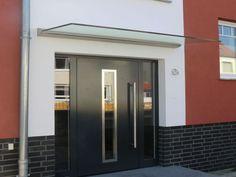 Edelstahlvordach Paderborn ein Echtglas Haustürvordach bei dem das Glas von einer Wandklemmleiste gehalten wird.