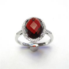 Garnet & Diamond Ring -  The faceted oval garnet weighs 4.15ct and is surrounded by a halo of diamonds. The ring is made from 14kt white gold. A332-103 (subject to prior sale) – Lilliane's Jewelry – 4101 W. 83rd St. Prairie Village, KS 66208 – 913-383-3376 –