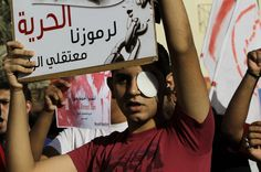 "Bahraini anti-government protester Mohamed al-Jazeeri, 16, who said he lost his left eye during previous clashes, raises a sign reading, ""Freedom to our symbols, prisoners of conscience,"" referring to jailed opposition leaders Thursday, June 7, 2012, in Sitra, Bahrain. The sign behind reads, ""Save Ahmed Oun,"" in English and Arabic, and ""Freedom for the injured, imprisoned Ahmed Oun."" (AP Photo/Hasan Jamali) #Bahrain #Protest"