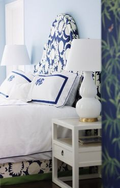 White and blue bedroom features pale blue walls framing white and blue headboard accented with matching bedskirt and white and blue monogrammed bedding flanked by white double gourd lamps with brass base atop ivory lacquered nightstands.