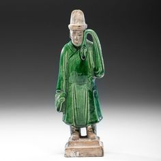 Ming Dynasty Tomb Figure. Chinese, Ming dynasty. A tomb pottery figure partially covered in a green glaze, standing on a pedestal. Ht. 10 in.