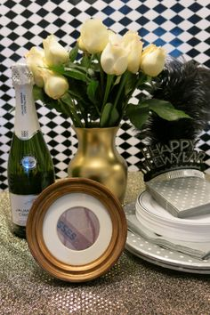"""Sequined fabric makes for the perfect New Year's Eve tablecloth. A spray-painted vase and a framed photo of a Hersey """"Kiss"""" wrapper adds spunk to this holiday tablescape. #partyplanning #events #holidaydecor #homedecor #DIY #newyearseve"""