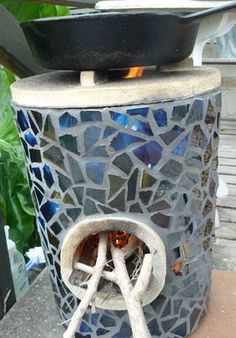 love this mosaic-ed rocket stove! cool beans for heating the greenhouse love this mosaic-ed rocket stove! cool beans for heating the greenhouse Diy Rocket Stove, Rocket Mass Heater, Rocket Stoves, Outdoor Oven, Outdoor Cooking, Stove Heater, Propane Stove, Tadelakt, Patio Fire Pits