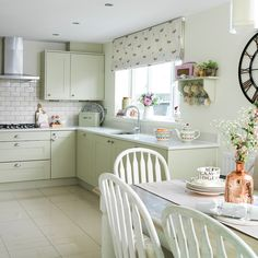 Nice kitchen design with light cabinets, floral blinds and white chairs