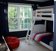 Navy walls, white bunk bed, but with a desk under it.