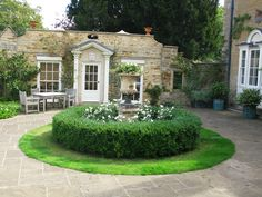 It is always good to incorporate original features when redesigning a garden as they are part of the history of the place. Here I used an original urn and plinth as the centrepiece to the formal garden which I surrounded with 'instant' box edging. The underplanting is of Anemone x hybrida 'Honorine Jobert' - this part of the garden faces north. Photography by Judith Sharpe