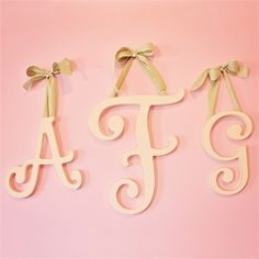 Spell out a name or a favorite phrase with the Large Cursive Wooden Hanging Letters from New Arrivals Inc.  Hand painted in cottage white and slightly distressed, these hanging wall letters come with your choice of ribbon