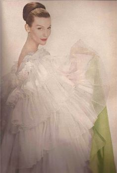 The Lily - She's all pale perfection. She flourishes in the shade and she looks as fragile as a Gautier heroine. The midsummer night's dream of an evening coat of silk organdie ruffles bound in satin by Galanos - The Flower Faces (Harper's Bazaar April 1956). Photography: Louise Dahl-Wolfe