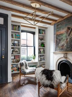 library with vintage fireplace, wood beams, modern lighting, sheepskins