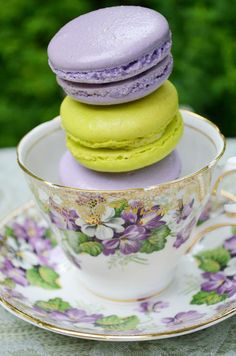 A trio of sweet macarons are stacked in a stunning teacup for a wedding rehearsal lunch in the garden.