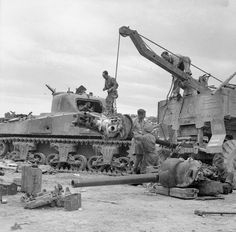 A 75mm gun being salvaged from a knocked-out Sherman tank by a Scammell Pioneer at 26th Armoured Brigade workshops in Perugia, 30th June 1944. The entry point for an 88mm shell can be seen on the side of the tank's hull