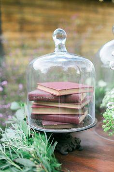 cute whimsical fairytale wedding decor idea: books in a cloche