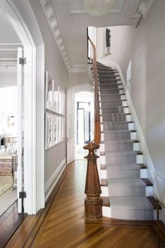 """""""I felt guilty about painting the wood moldings,"""" Roeder confesses. """"But they felt heavy and dated the space."""" Painting the stair risers white and adding a runner also gave the grand staircase a lighter touch. The floors were stripped and then refinished."""
