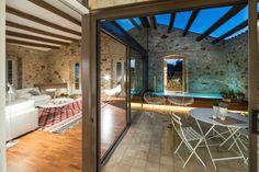 Un vecchio granaio trasformato in una mansarda piena di luce, che mantiene la struttura originale con pareti in pietra e travi in legno.