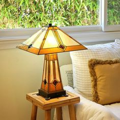 @Overstock.com - Classic Tiffany-style table lamps add timeless style to your home. This gold and bronze Mission style lamp is made of hand-cut pieces of stained glass trimmed in copper foil. The lamp has three settings and smoothly functions with a pull chain.http://www.overstock.com/Home-Garden/Tiffany-Style-Golden-Mission-Table-Lamp-with-Lit-Base/7217899/product.html?CID=214117 $139.99