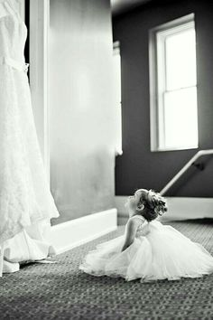 Adorable picture of the flower girl looking at the bride's gown.